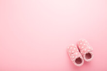 Beautiful Soft Warm Baby Girl Slippers On Light Pink Table Background. Pastel Color. Closeup. Comfortable Home Shoes. Empty Place For Text. Top Down View.