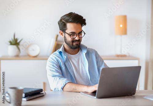 Obraz Smiling Arab Man Self-Entrepreneur Working With Laptop At Home Office - fototapety do salonu