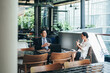 Business colleagues discussing work at office cafeteria.  Businessman and businesswoman sitting at cafe and talking about investment ideas and cooperation plans together