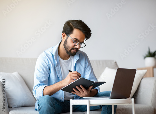 Fototapeta Young Arab Freelancer Man Taking Notes And Working On Laptop At Home