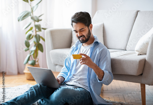 Obraz na plátně Millennial Arab Guy Making Payments With Laptop And Credit Card At Home