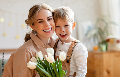 Grateful mother with bouquet hugging son #414697235