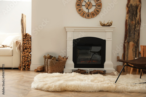 Beautiful fireplace and basket with firewood in contemporary room interior Fototapeta