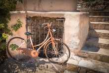 Rusted Bike Standing For A Abndoned House With Stone Stairs On Kythira, Greece