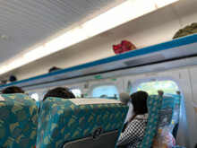 Train Economy Standard Seats Show Each Row Of 5 Seats In A 2×3 Pattern, Each Seat Has A Fold-down Table Tray. People Quietly Sit In The Train And Light Is On The Whole Trip.