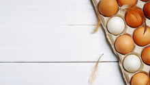 Top View Of Raw Organic Chicken Eggs In Egg Carton With Chicken Feather On White Wooden Background.