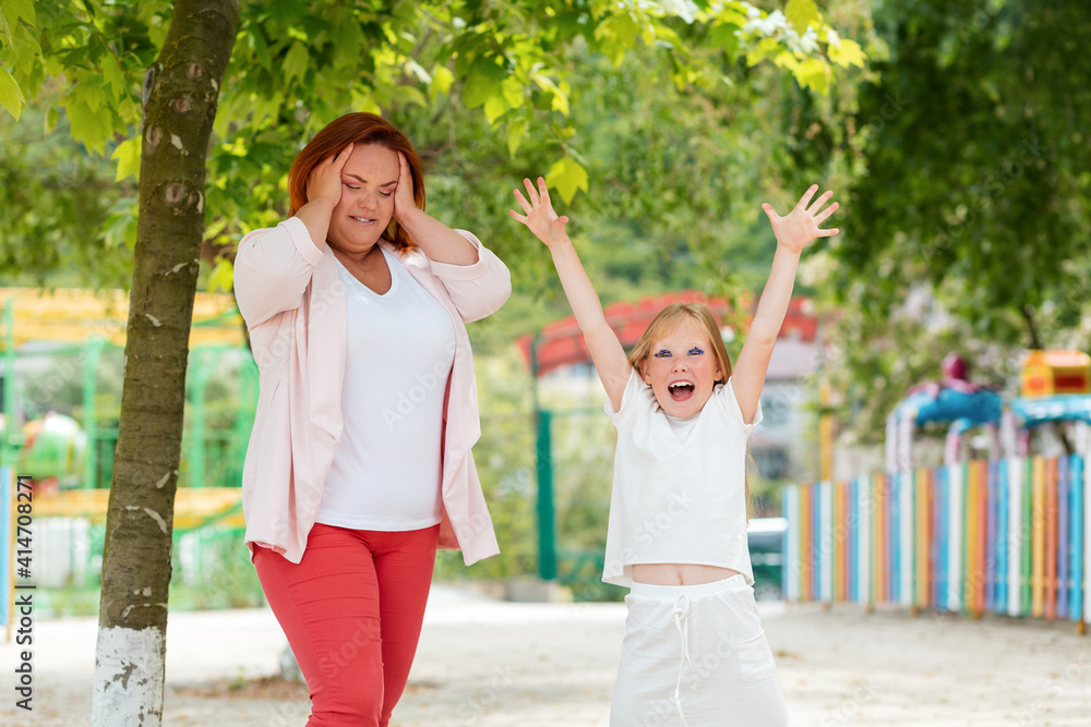 Fototapeta Family. A worried mother with a cheerful daughter in the Park. The concept of children's whims and difficulties in raising children
