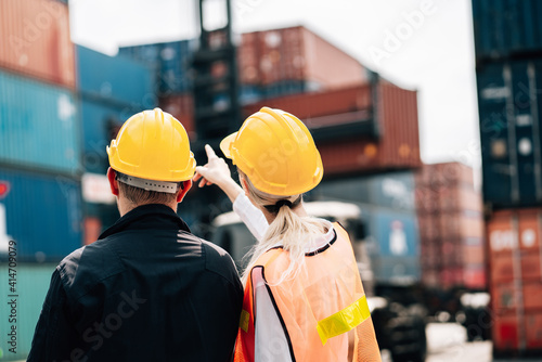 Obraz na plátne workers teamwork man and woman in safety jumpsuit workwear with yellow hardhat and use laptop check container at cargo shipping warehouse