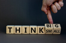 Think Small Or Big Concept. Businessman Turns Wooden Cubes, Changes Words 'think Small' To 'think Big' Or Vice Versa. Beautiful Grey Background. Business And Think Small Or Big Concept. Copy Space.