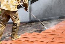 Professional In Uniform Using High Pressure Machine To Clean Rooftop From Dirt And Lichen. Before And After Situation. Clean And Dirty Roof Tiles.