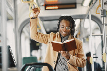 African American Man Riding In The City Bus. Guy In A Brown Coat. Man With Notebook.