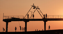 A Lot Of People Are Relaxing At The Amazing Sunset Of The Day. Active Rest At Sea. Shadow Drawing Of People. Sunbathe, Jump, Talk On A Building Structure, Building, Building, The Setting Sun. Fish Far