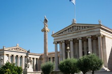 Academy Of Athens Neoclassical Building With Statues, Flag And Blue Sky