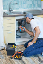 Plumbing Troubles. Professional Plumber Using Pipe Wrench While Examining And Fixing Sink Pipe In The Kitchen