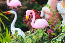 Close-up Photo Of A Pink Flamingo Statue, A Pink Flamingo Statue In An Ornamental Garden.