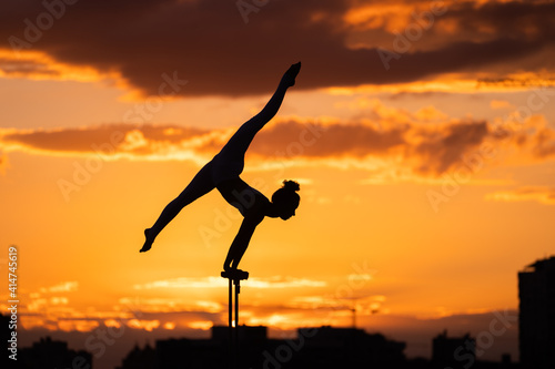 Fotografie, Tablou Silhouette of female circus artist doing handstand on the dramatic sky backgroun