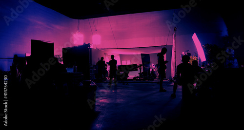 Fototapeta Behind the scenes of shooting video production and lighting set for filming movie which film crew team working in silhouette and professional equipment in studio for video online. video production con obraz