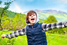 Happy Boy Joyfully Screams In The Mountains With His Arms Outstretched To The Side. Relax In A Mountains. Hello Springtime. Greeting. Laughing Joyful Child Meets Spring In The Open Air. Joyful People