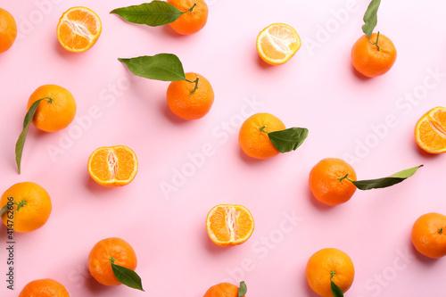 Fototapeta Fresh ripe tangerines with green leaves on pink background, flat lay obraz