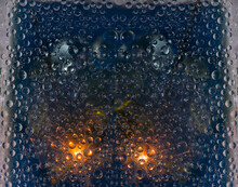 Freezing Raindrops Are Located Against The Background Of A Window Glass With The Car's Headlights Reflected In It. 3D Render.