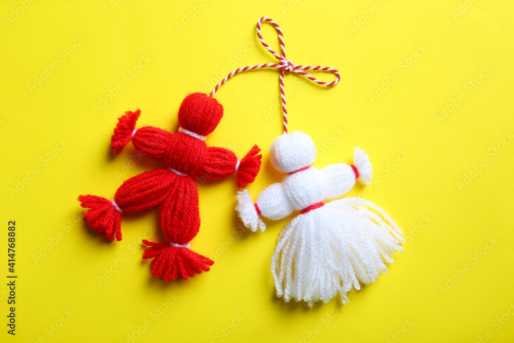 Fototapeta Traditional martisor shaped as man and woman on yellow background, top view. Beginning of spring celebration