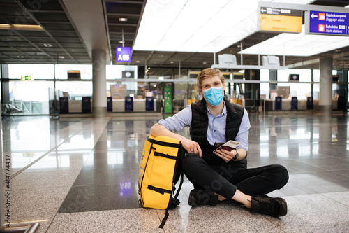 Fotografia, Obraz A man wearing medical face mask while sitting on the airport floor