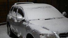 Snow-covered Car At Night. Snow Falling Asleep SUV. The Damaged Car Is Under The Snow.