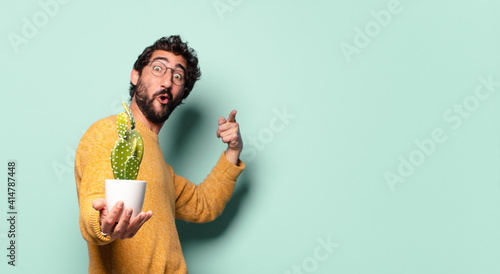 Cuadros en Lienzo young crazy bearded man holding a cactus house plant