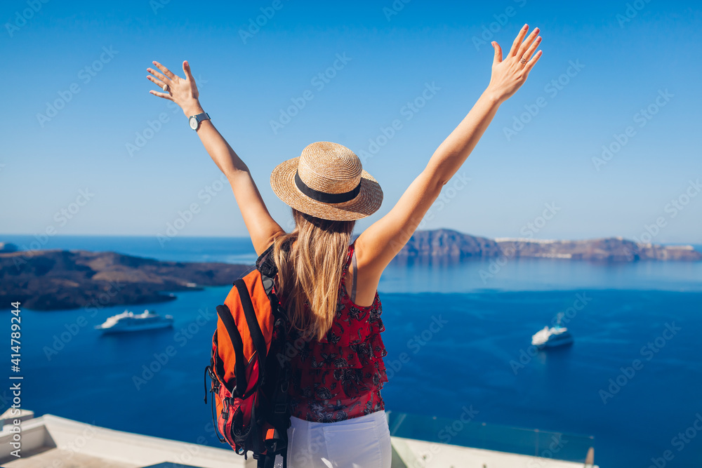 Fototapeta Happy woman traveler walking raising hands in Thera, Santorini island, Greece enjoying sea landscape. Summer vacation