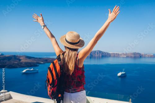 Fototapeta Happy woman traveler walking raising hands in Thera, Santorini island, Greece enjoying sea landscape. Summer vacation obraz