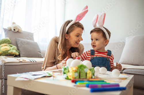 Fototapeta Having fun during Easter preparation. Portrait of pretty young mother hugging little boy while celebrating Easter at home, copy space. Mother and son painting easter eggs obraz