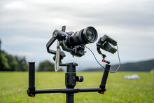 Camera In A Professional Video Recording Set Planted On The Ground, On Top Of A Gimbal / Stabilizer With Included Screen. Green Background In The Middle Of Mountains.