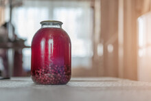 Big Glass Jar With Canned Red Compote Stands On Kitchen Table