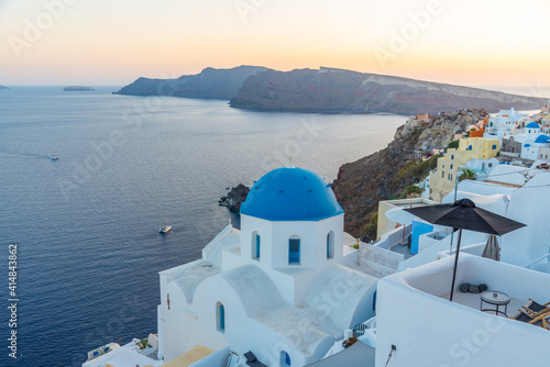 Sunset view of churches and blue cupolas of Oia town at Santorini, Greece Wallpaper Mural