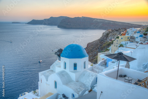 Sunset view of churches and blue cupolas of Oia town at Santorini, Greece Fotobehang