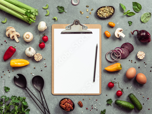 Fototapeta Food ingredients, salad serving utensils and clipboard with white paper sheet. Various of vegetarian cooking ingredients on gray background.Recipe book concept.Copy space for text.Top view or flat lay obraz