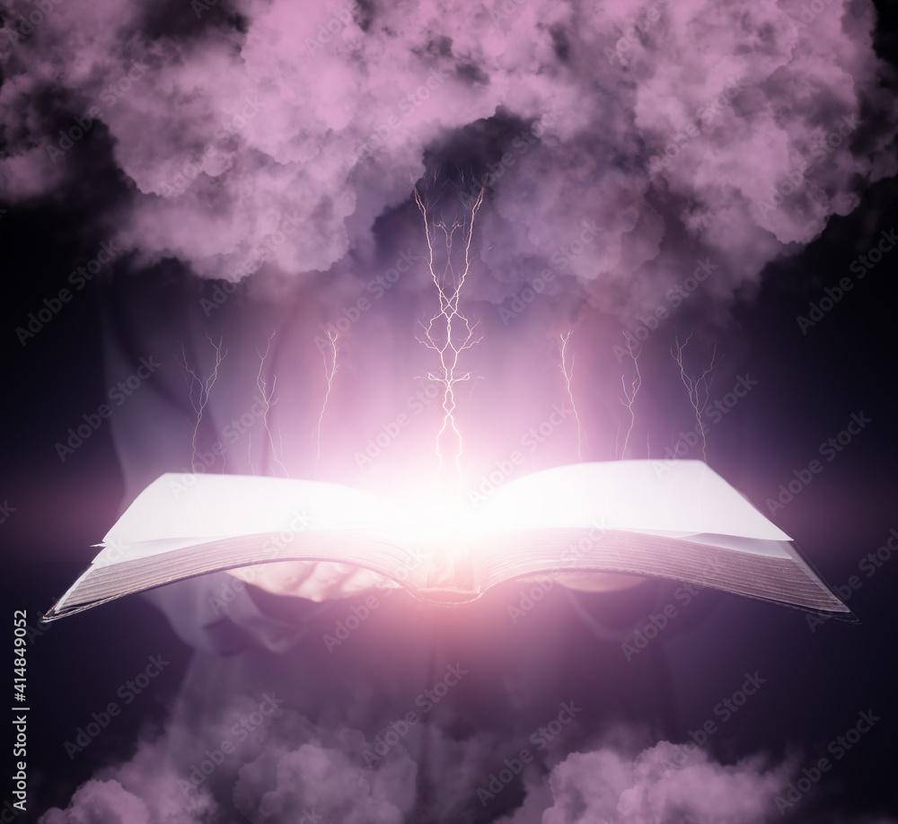 Fototapeta Wizard with open spell book on dark background