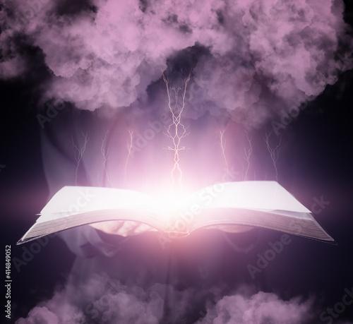 Wizard with open spell book on dark background © Pixel-Shot