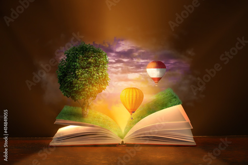 Fototapeta Open magic book with flying hot air balloons and growing tree on dark background obraz