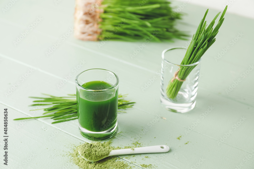 Fototapeta Glass with fresh wheatgrass juice and powder on color wooden background