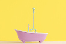 Toy Bathroom With Shower For Doll On Yellow Background. Infant Washing And Bathing. Hygiene And Care Of Young Children