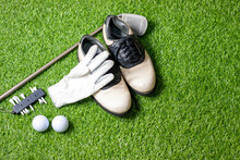Golf Ball With Golf Shoes And Glove On Green Grass