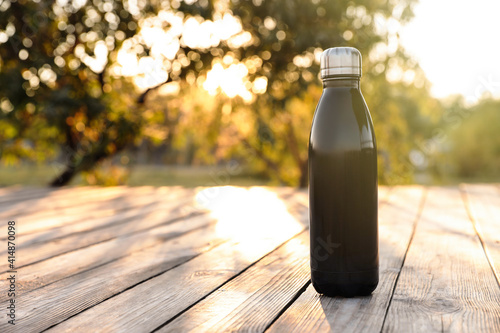 Modern black thermos bottle on wooden surface outdoors. Space for text