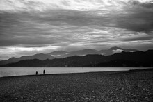 Pebbly Beach, Sea, Silhouette Of Mountains And Cloudy Sky At Evening