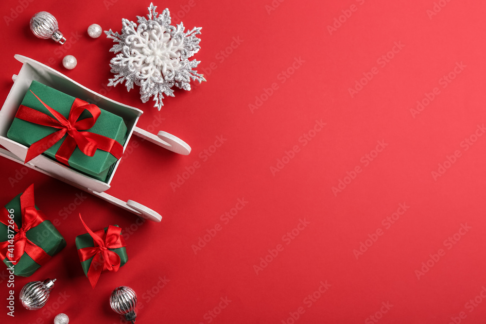 Fototapeta Beautiful Christmas composition with miniature sleigh on red background, flat lay. Space for text