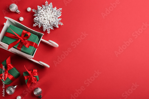Fototapeta Beautiful Christmas composition with miniature sleigh on red background, flat lay. Space for text obraz