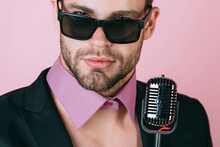 Gay Man In Glasses Sing In Microphone. Sexy Dj Young Man On Pink Background. Music, Look And Retro Style. Freak Singer With Stylish Retro Microphone. Karaoke Singer
