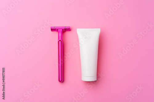 Shaving gel and disposable shaver on pink background top view