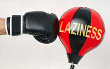 Overcome Laziness. Stop Being Lazy Concept. Beat The Procrastination Concept With A Strong Man's Hand In A Boxing Glove Hits The Punching Bag With Text Laziness. Motivation Background.