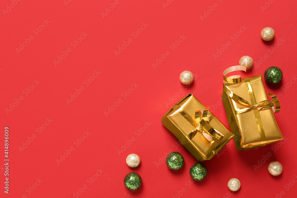 Fototapeta Gift boxes and Christmas balls on red background, flat lay. Space for text